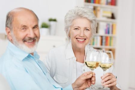 jubilados: Feliz pareja senior sentados juntos en un sofá brindando con copas de vino blanco en la celebración de un año juntos