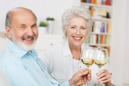 people celebrating: Happy senior couple sitting close together on a sofa toasting each other with glasses of white wine as they celebrate another year together Stock Photo