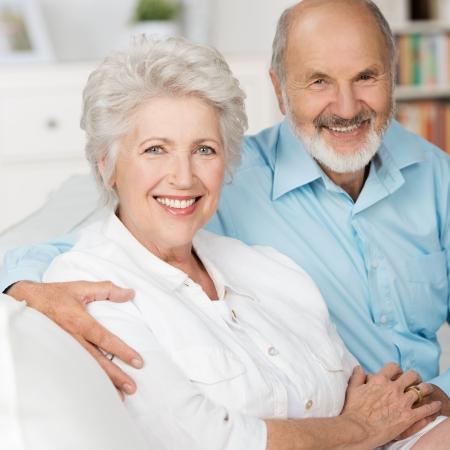 jubilados: Romántica pareja de ancianos sentados juntos en un sofá en su sala de estar en un amoroso abrazo sonriendo a la cámara