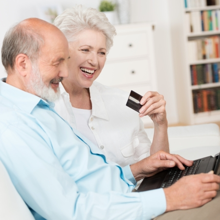 Senior couple buying online sitting together on a sofa with their laptop computer and bank card laughing as they make their choice photo