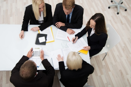 High angle view of a group of young successful businesspeople in a meeting analysing and planning a new strategy