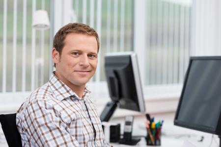 카메라를 찾고 자신의 컴퓨터, 머리의 앞면과 어깨에있는 사무실에서 그의 책상에 잘 생긴 웃는 캐주얼 사업가
