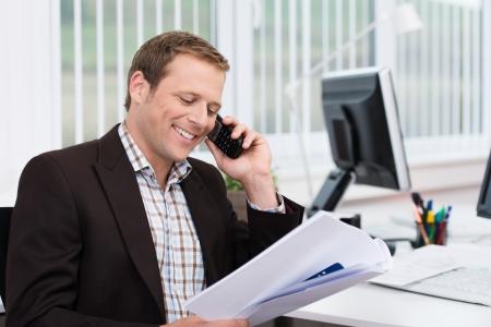 přátelský: Efektivní podnikatel odpovídání na telefonní hovor v kanceláři diskutovat dokument, že je drží v ruce Reklamní fotografie