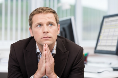 perturbed: Worried pensive businessman sitting at his desk staring off into space with his hands folded under his chin Stock Photo