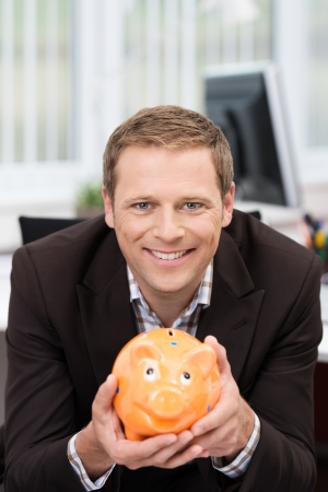 financial security: Handsome friendly young businessman holding a piggy bank in his hands as he plans his financial investments to ensure security for his retirement
