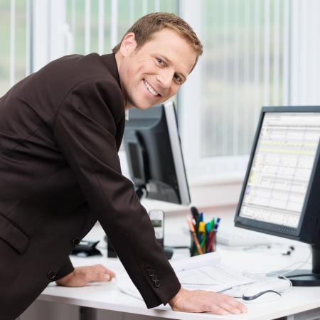 自信を持って成功した若い実業家彼の机に彼の腕をもたれ、カメラに笑顔を彼のコンピューター回転に情報を表示するには