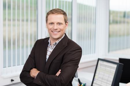 자신감 비즈니스 리더 또는 그의 팔 사무실에서 그의 책상에 기대어 매니저 서 카메라에 미소를 접혀