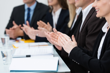 acknowledgement: Close up view of diverse businesspeople in a meeting applauding and clapping their hands in recognition of an achievement or in praise Stock Photo