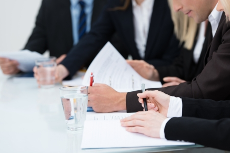 management meeting: Close up view of the hands of business people taking notes in a meeting seated at a table Stock Photo