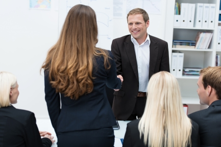 congratulating: Two business people, a man and woman, shaking hands across a table in a meeting sealing an agreement or business deal Stock Photo