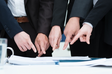 objection: Group of businesspeople pointing to a document on a desk, close up cropped view of their hands