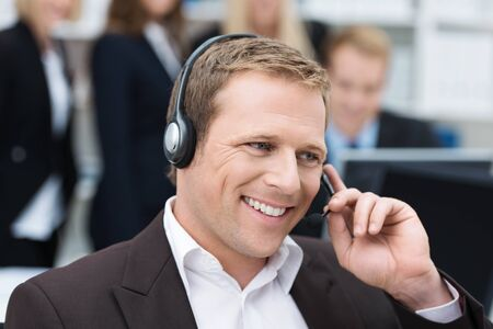 call center representative: Handsome young businessman with a warm smile taking a call on a headset as he deals with queries at the customer support call centre