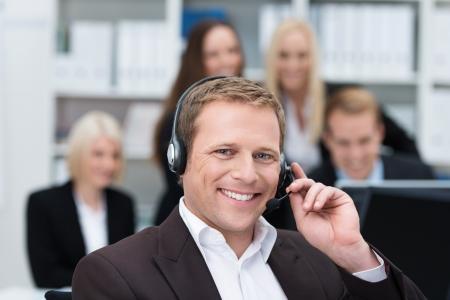 hands free: Sonriendo apuesto hombre de negocios joven que usa un receptor de cabeza en la oficina para facilitar la comunicaci�n de manos libres o recibir llamadas en un centro de llamadas