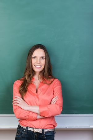 Confident successful beautiful young woman standing with her arms folded in front of a blank green blackboard with copyspace photo