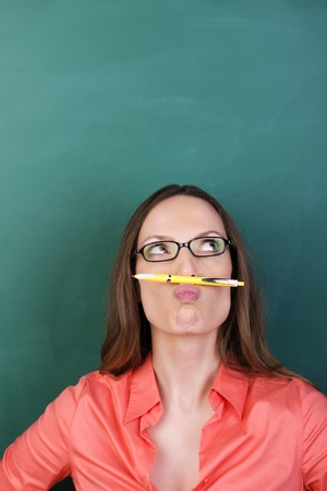 contemplated: Thoughtful playful woman with a pencil moustache and glasses standing against a green background looking upwards with a pensive expression Stock Photo