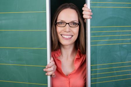 Smiling woman or teacher in glasses peering between two blank green chalkboards photo
