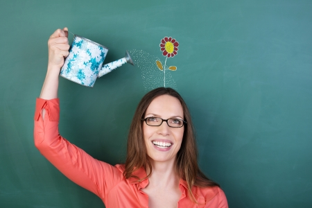 Conceptual image of a laughing young woman wearing glasses watering a flower on her head that has been drawn on the blackboard behind her with a small tin watering can