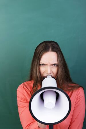 verbal: Angry young woman with a megaphone raised to her lips and a frown on her face in front of a green background with copyspace