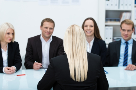 Young female job applicant in an interview sitting with her back to the camera facing a row of personnel executives photo