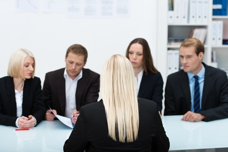 Human resources team conducting an interview reading the credentials of a blond business applicant sitting with her back to the camera photo