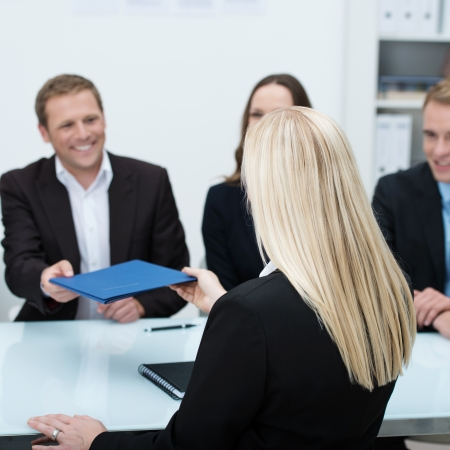 executive job search: Young blond female job applicant sitting with her back to the camera handing over her curriculum vitae to a smiling businessman conducting the interview