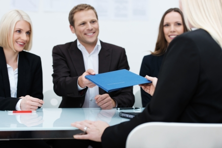 consultation: Business team of smiling professionals conducting a job interview reaching to take the file of credentials from the female applicant
