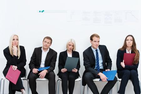 entrevista: Grupo de los solicitantes de un puesto vacante o de trabajo en una empresa que se sienta en una larga fila con las carpetas que contienen sus credenciales ignorando cuidadosamente entre sí