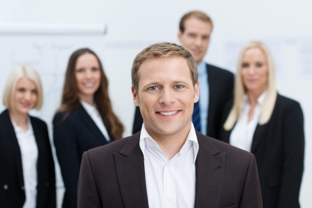manager team: Handsome friendly young manager or team leader with a confident smile posing in front of his team with shallow dof Stock Photo