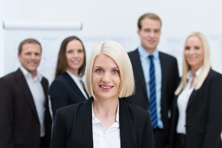 manager team: Blond Caucasian female young manager smiling with a young happy professional team behind her