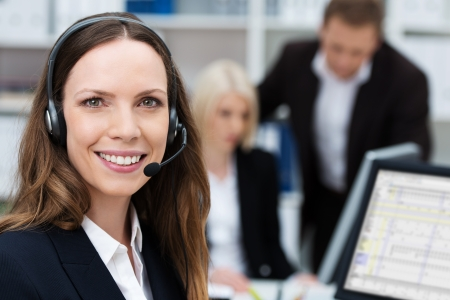 prospection: Friendly attractive young call centre operator or member of the client services team wearing a headset turning to give the camera a lovely warm smile