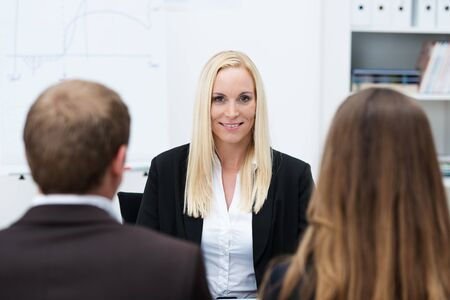 Smiling confident blond businesswoman being interviewed for a post by a man and woman with their backs to the camera photo