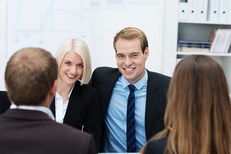 Confident young business team with a smiling handsome man and woman sitting side by side in a meeting facing the camera, view between a man and a woman with their backs to the camera photo