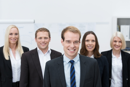 handsom: Handsom young Caucasian manager smiling with a happy team made of three women and a man, behind him