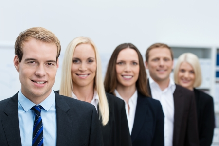 Serious handsome young business manager with his successful team of diverse business people lined up behind him photo