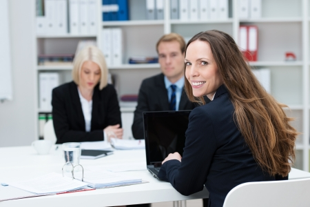 turning table: Businesswoman in a meeting sitting with coworkers at a table in the office turning in her chair to smile at the camera