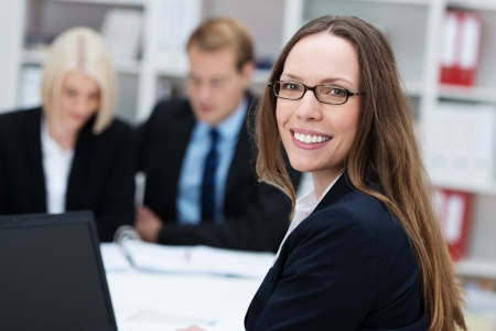 project manager: Friendly happy businesswoman wearing glasses with long straight brunette hair turning to smile at the camera while working in an office with her colleagues