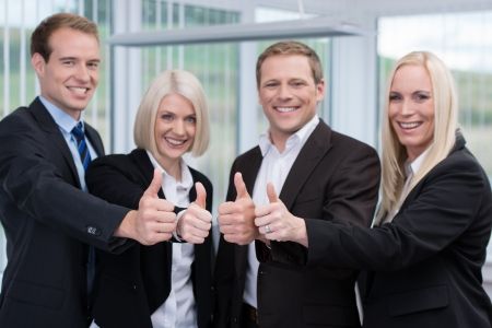 Successful motivated young business team giving a thumbs up gesture of success, approval and agreement photo