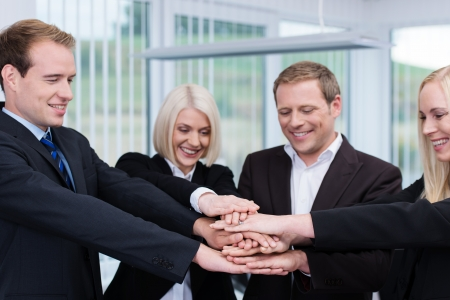 manos unidas: Trabajo en equipo - una imagen conceptual de un grupo de compañeros de trabajo corporativos de pie en un círculo colocando sus manos una encima de la otra para mostrar la cooperación y trabajo en equipo