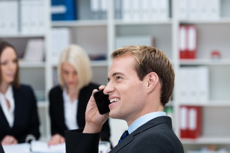 empleados trabajando: Hombre de negocios feliz hablando por su teléfono móvil en la oficina con sus colegas ocupados trabajando en segundo plano