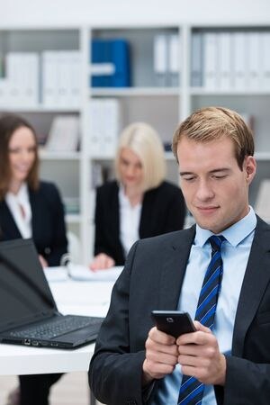 pda: Businessman reading a text message on his mobile phone while sitting in a busy corporate office