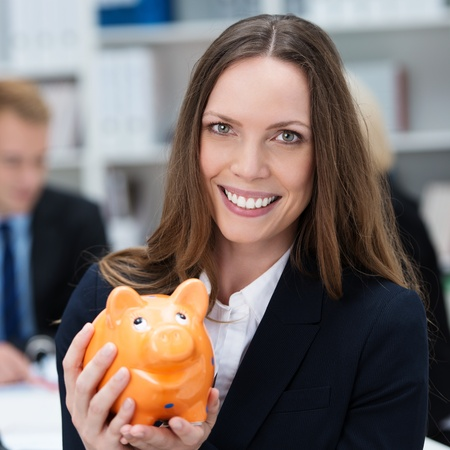 Attractive smiling business woman holding a piggy bank