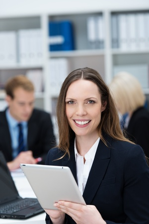 Attractive young businesswoman with a friendly confident smile holding a tablet-pc in her hands at the office photo