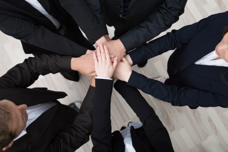 co workers: Teamwork - conceptual image of a group of young professional businesspeople standing in a circle facing each other clasping hands Stock Photo