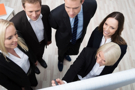High angle view of a young female teamleader or businesswoman giving a presentation to a group of young business people on her team using a flipchart photo