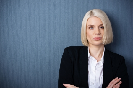 arrogance: Beautiful stylish confident female business executive standing with folded arms looking at the camera with a serious expression, head and shoulders portrait Stock Photo