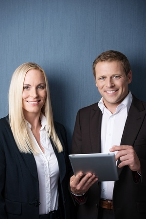 Business colleagues, a stylish young man and woman, having a chat looking at information together on a tablet-pc photo