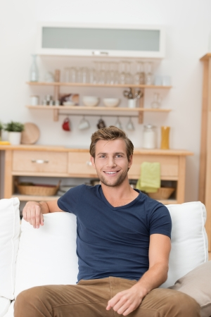 Handsome unshaven casual youn man sitting on a sofa at home relaxing and giving the viewer a friendly smile photo