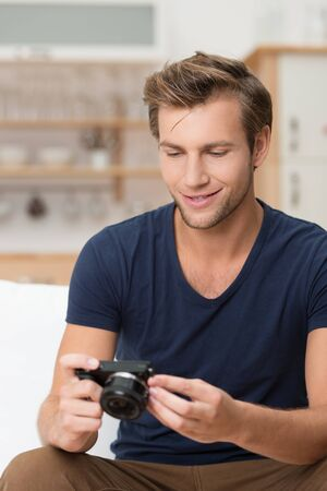 Handsome casual young man smiling as he checks an image on his camera after photographing something indoors Stock Photo - 22345699