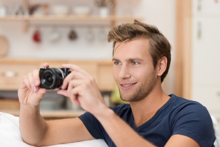 photographing: Handsome young man taking a photograph indoors lining up the camera composing the image and focusing