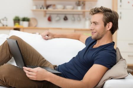 ležérní: Mladý muž relaxační s přenosným počítačem, ležící zpět na gauči doma, čtení informací na obrazovce